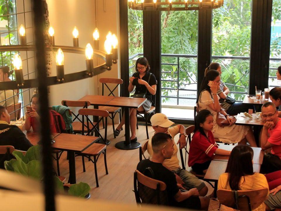 khách hàng cảm nhận sự thoải mái khi ngồi bàn ghế nội thất pcm cung cấp cho quán cafe